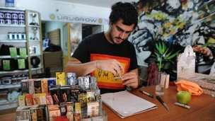 Juan Manuel, owner of the first shop dedicated to cannabis merchandising in Montevideo, rolls a cannabis cigarette at his shop counter