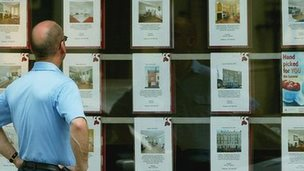 A man looks at houses in an estate agent window
