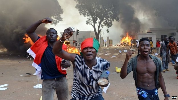 Men shout slogans in front of burning cars, near the Burkina Faso's parliament - 30 October 2014,  Ouagadougou, Burkina Faso