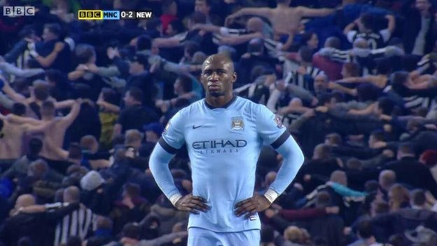 Newcastle fans celebrate leading the game in front of Eliaquim Mangala