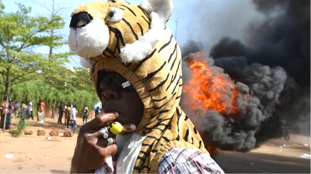 A man wearing a tiger costume hat stands outside parliament in Ouagadougou in Burkina Faso as cars and documents burn behind him