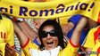 A Romanian football supporter holds up a football scarf