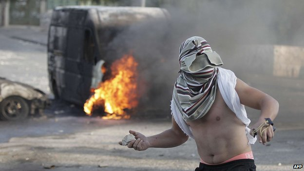 A masked Palestinian youth throws a rock during clashes with Israeli security forces in east Jerusalem on October 30, 2014.