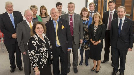 Sir Ron Watson CBE hand with new chair Sue Musson and the rest of the board