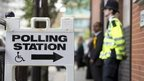 A police officer stands outside a polling station in Tower Hamlets