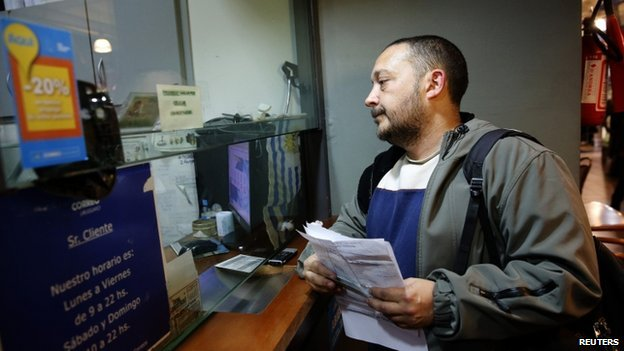 A man waits to register as a marijuana home grower at a postal office in Montevideo August 27, 2014