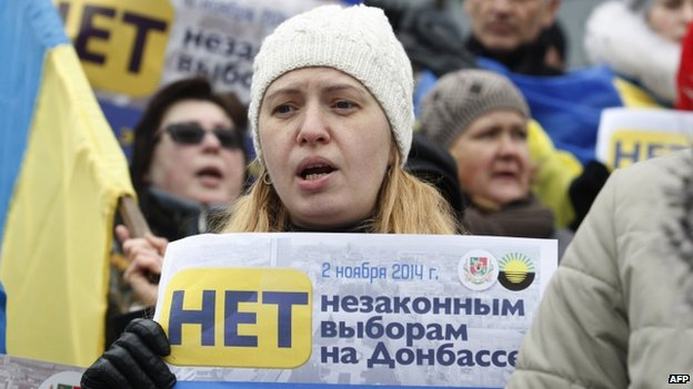 "A woman in Kiev holds placard ""Donbas is Ukraine! No illegal voting in Donbas!"""