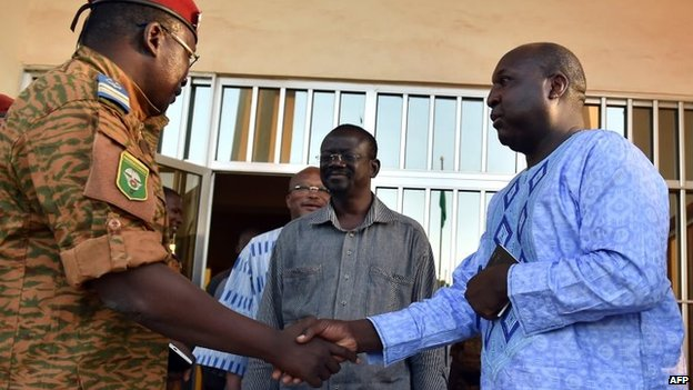 Burkinese Lieutenant-Colonel and interim leader Isaac Zida (L) escorts opposition leaders Zephirin Diabre (R), Benewende Sankara (C) and Roch Marc Christian Kabore (rear) at the end of a meeting between the army and opposition leaders in Ouagadougou, 2 November 2014