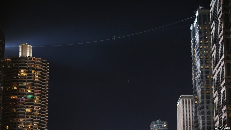 Nik Wallenda walks on a wire from Chicago's Marina City's tower to Leo Burnett building