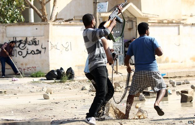 Armed civilians load a heavy machine gun with bullets during clashes with Islamist militiamen in Benghazi November 2014