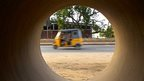 Rickshaw through a concrete pipe