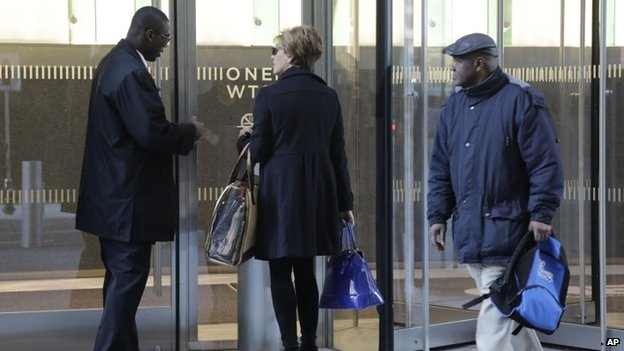 A doorman holds the door for an employee entering One World Trade Center, 3 November 2014