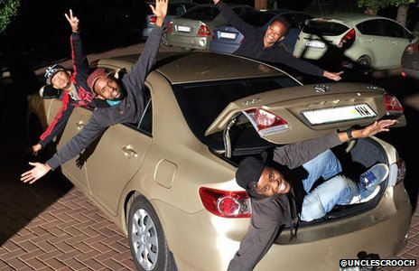 Three men leaning out of a car with their arms outstretched
