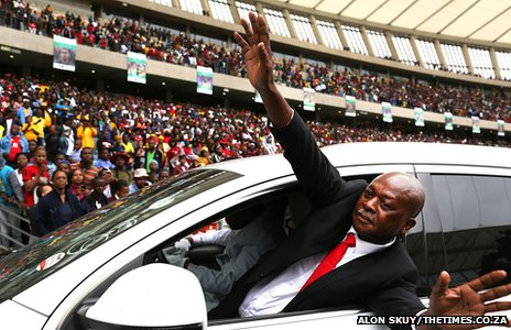Samuel Meyiwa leaning out of a car with his arms outstretched