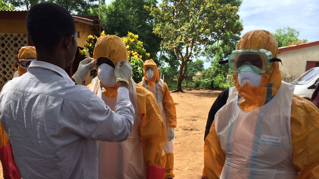 A burial team in Sierra Leone suits up in their protective gear