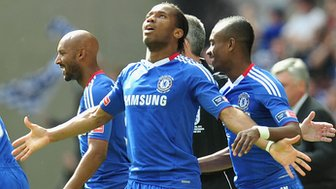 Didier Drogba in Chelsea football kit, looking to the sky with arms wide open.