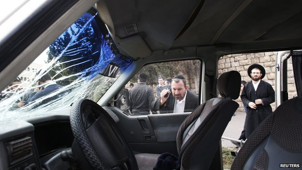 An ultra-Orthodox Jewish man looks into the vehicle of a Palestinian motorist who rammed into pedestrians near the scene of the attack in Jerusalem November 5, 2014