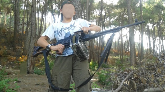 A 13-year-old boy who wishes to be named 'Abu Hattab' stands in a forest holding a weapon