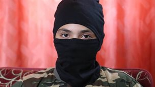 A 13-year-old boy who wishes to be named 'Abu Hattab' sits wearing a black balaclava