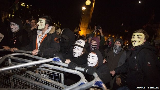 "Anti-capitalist protesters wearing Guy Fawkes masks remove police barricades during the ""Million Masks March"" in Parliament Square"
