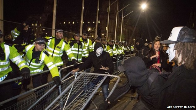Protesters wearing Guy Fawkes masks clash with police