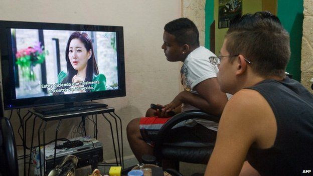 Two Cuban men watch a South Korean soap opera