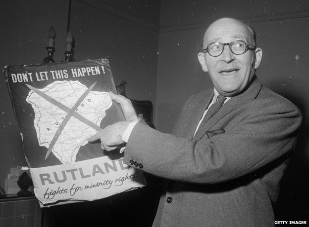 Sir Kenneth Ruddle, chairman of Rutland County Council, holds up a poster condemning the governments plans to incorporate the ancient county of Rutland into neighbouring Leicestershire