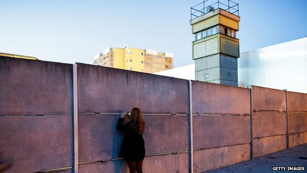 "A visitor peeks into the former ""death strip"" between layers of the former Berlin Wall next to a former East German guard tower at the Berlin Wall Memorial at Bernauer Strasse. 8 Nov 2014"