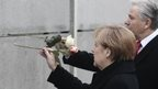 German Chancellor Merkel puts rose into a remaining section of the Wall - 9 November