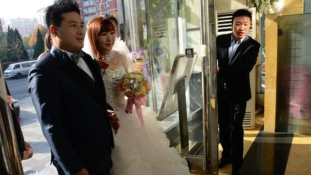A newly-married couple (C) walk into a restaurant near the China National Convention Center (CNCC), where the annual Asia-Pacific Economic Cooperation (APEC) Summit is being held in Beijing on November 8, 2014