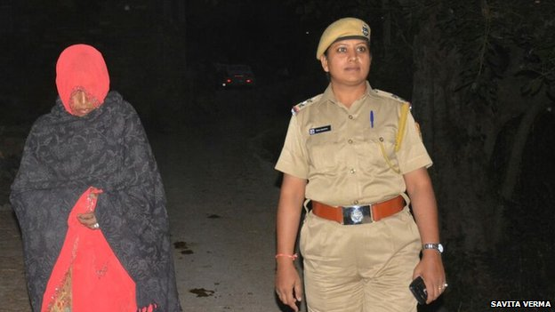 The 45-year-old woman (left) with a police officer