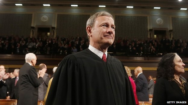 Supreme Court Chief Justice John Roberts stands at the 2014 State of the Union address.
