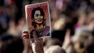 A man holds on 16 June, 2012 a poster of Myanmar opposition leader Aung San Suu Kyi during a public meeting following a ceremony where Suu Kyi formally accepted her Nobel Peace Prize in Oslo