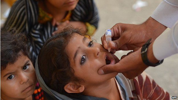 A Pakistani health worker administers the polio vaccine to a child during a vaccination campaign in Bannu on 25 June 2014.