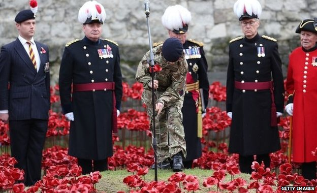 Military cadet Harry Alexander Hayes places the last ceramic poppy in the moat of the Tower of London to mark Armistice Day on 11 November 2014