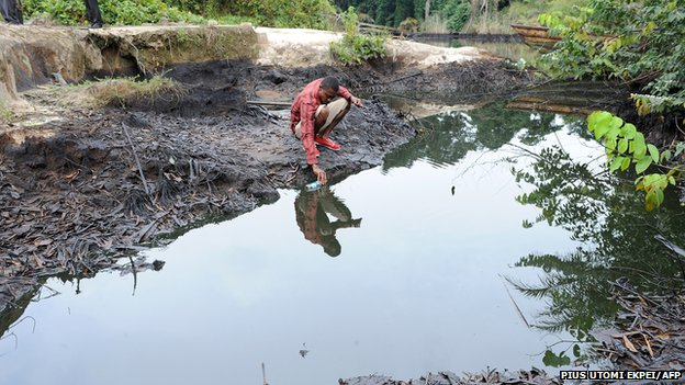 A man scoops spilled crude oil allegedly caused by Shell equipment failure floating at the bank of B-Dere waterways in Ogoniland, Rivers State, on August 11, 2011