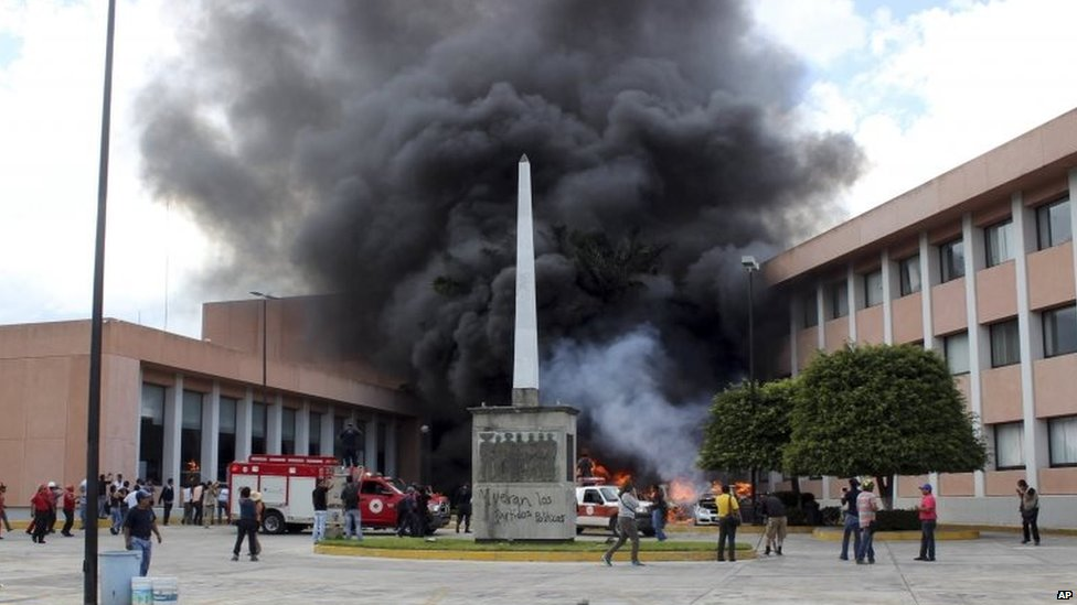 Firefighters arrive to try to extinguish several burning vehicles in front of the state congress in Chilpancingo on 12 November, 2014.