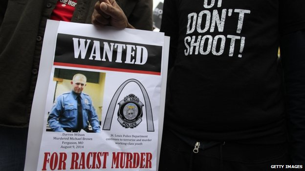 Demonstrators holds a sign on October, 11 2014 in St. Louis, Missouri, as they protest the shooting death of Michael Brown.