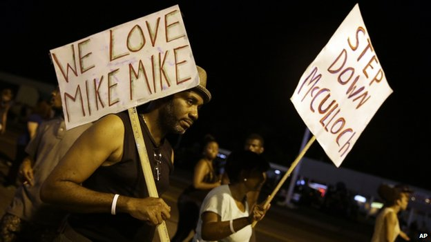 Protesters in Ferguson with signs calling for the removal of the prosecutor, Robert McCulloch, from the case.