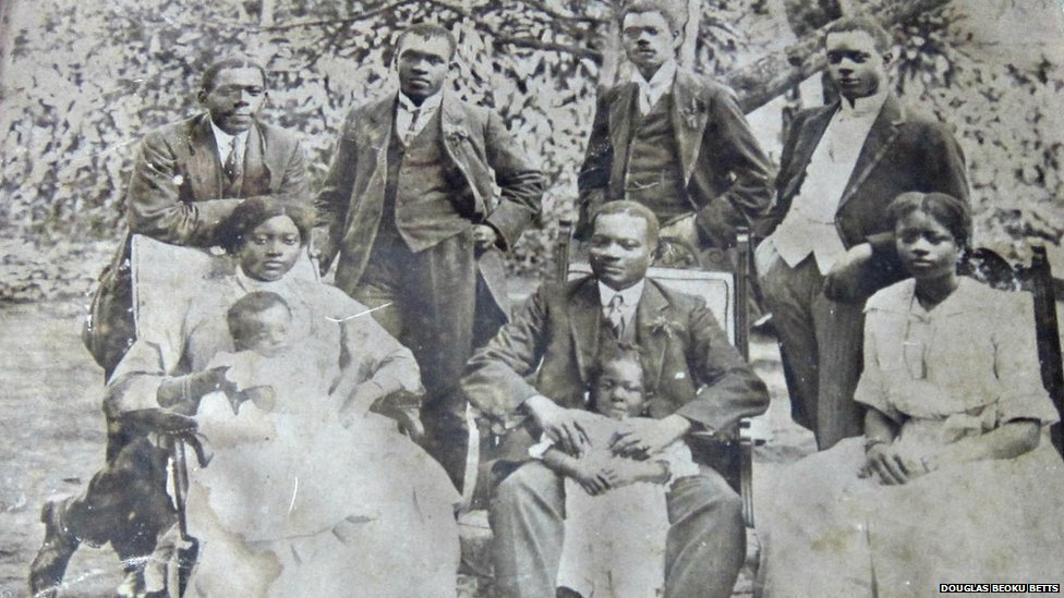 A family photograph of two women and one man seated, one woman and the man with infants on their knee, with four men standing behind. Everyone is dressed very smartly, the men in tailored three-piece suits, and the women in full length cotton dresses, hair tied back.