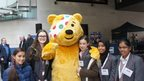 Pudsey poses with the School Reporters, Tony Hall is in the background.