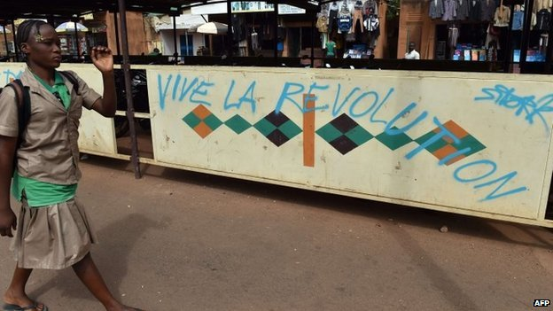 "A schoolgirl walks past graffiti ""Blaise go away"" ""Long live the revolution"" on November 6, 2014 in Ouagadougou"