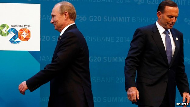 Australian Prime Minister Tony Abbott (R) reacts after officially welcoming Russian President Vladimir Putin to the G20 summit in Brisbane, Australia on 15 November 2014