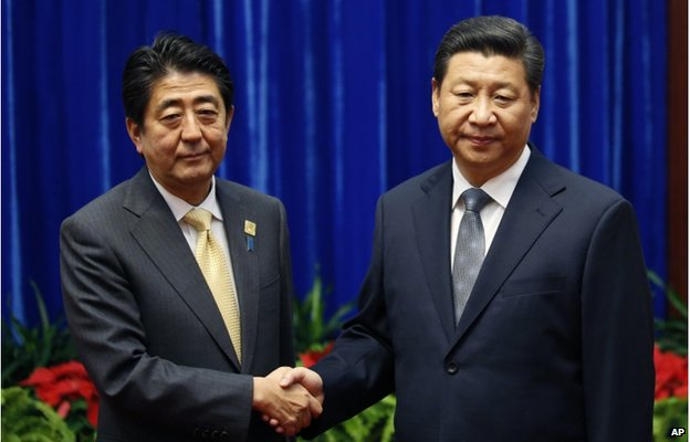 In this 10 Nov 2014, file photo, Japan's Prime Minister Shinzo Abe, left, and China's President Xi Jinping, right, shake hands during their meeting at the Great Hall of the People, on the sidelines of the Asia-Pacific Economic Cooperation (APEC) summit, in Beijing.