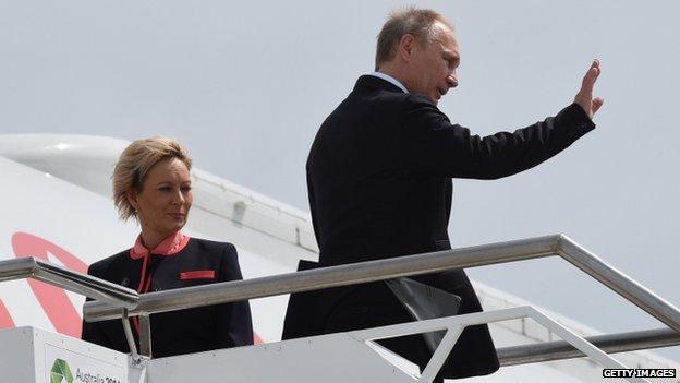 President Vladimir Putin (R) waving goodbye as he leaves the G20 Summit, at the airport in Brisbane