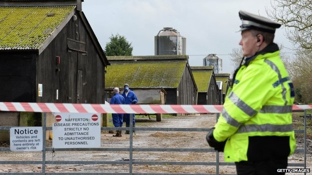 A policeman stands guard at a farm in Nafferton, East Yorkshire, where a strain of bird flu has been confirmed