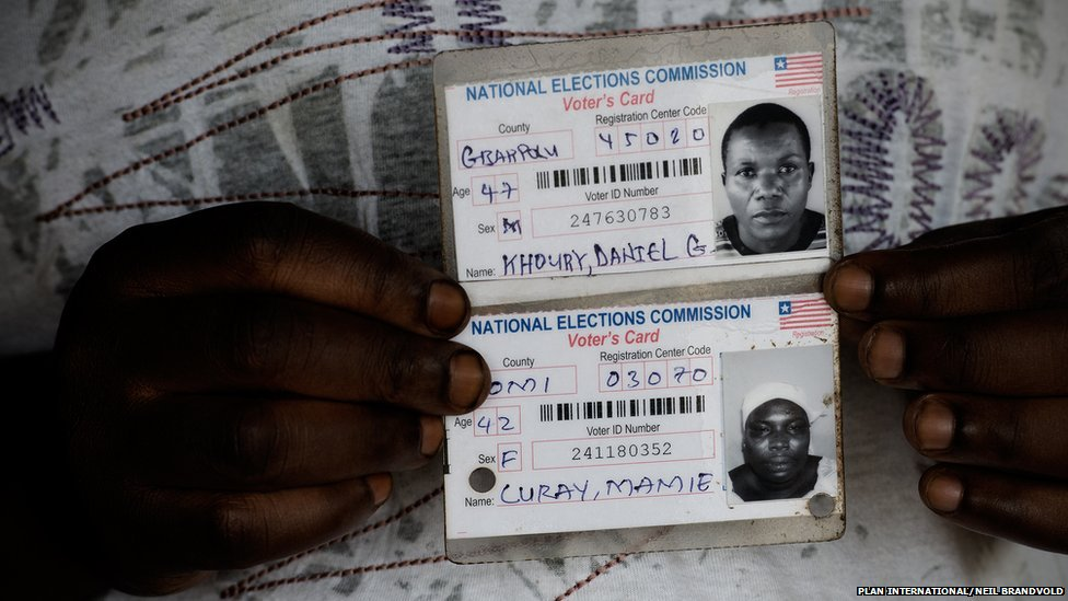 Fatu, 32, with parents' ID cards, the only pictures they have of them
