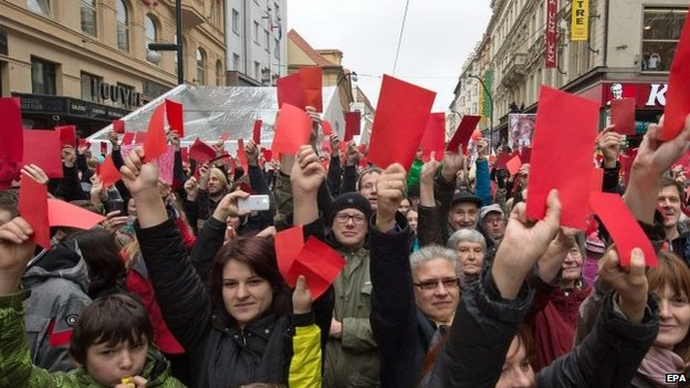 Protesters show symbolic red cards during a protest in Prague, Czech Republic on 17 November 2014