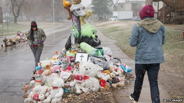 Rebeca Maldonado (L), of Chicago, and Aaron Jeremiah, of Houston, visit a memorial near the location where 18-year-old Michael Brown was shot  in Ferguson, Missouri 16  November 2014