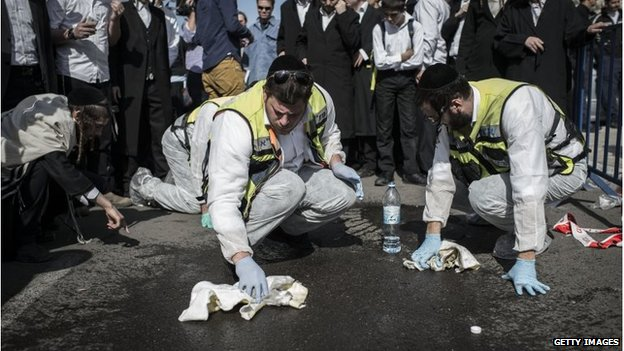 Israeli emergency personnel clean the site outside a synagogue